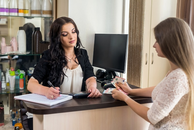 Amministratore di salone di bellezza e cliente con banconote in euro