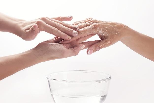 Salone di bellezza, applicare crema idratante sulle mani e massaggiare