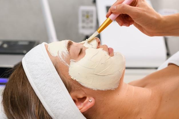 Il cosmetologo del trattamento professionale per la cura della pelle del salone di bellezza applica una maschera peeling all'argilla alginato del viso bianco