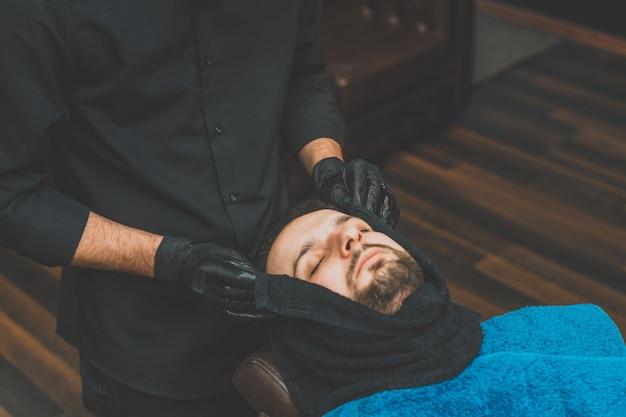 Negozio di bellezza per uomo. radersi la barba in un barbiere. il barbiere si taglia la barba con un rasoio e un tagliatore. vicino tagli di capelli brutali. attrezzature per parrucchieri. messa a fuoco selettiva.
