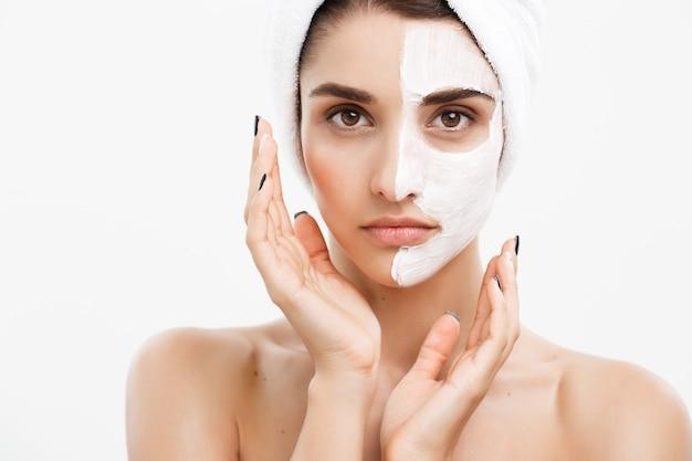 Concetto di cura di pelle di bellezza - bello ritratto caucasico del fronte della donna che applica la maschera crema sulla sua parete bianca della pelle facciale.