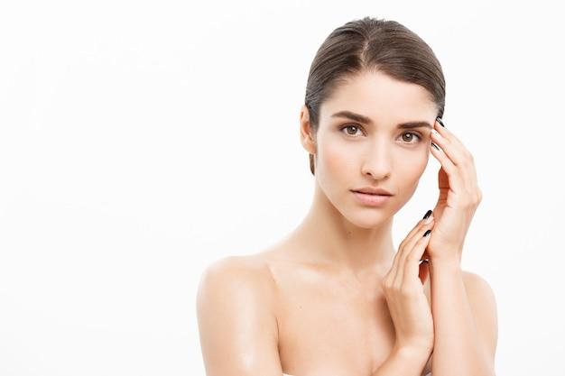 Concetto di cura della pelle bellezza bella donna caucasica viso ritratto bella bellezza giovane modello femminile ragazza che tocca il suo viso pelle guance mani dita moda modello di bellezza isolato su bianco