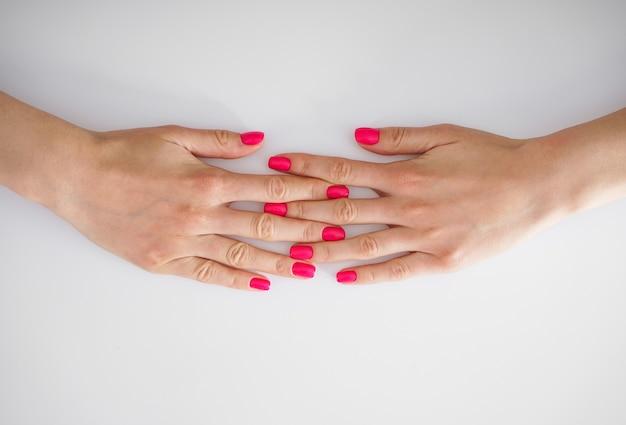 Concetto di bellezza e cura della pelle. belle mani di una giovane donna e bella manicure su uno sfondo bianco, flat-lay.