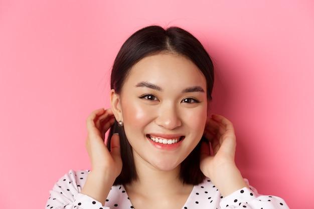 Concetto di bellezza e cura della pelle. primo piano di un'adorabile donna asiatica sorridente che si infila i capelli dietro le orecchie, arrossendo e guardando la telecamera, in piedi su sfondo rosa