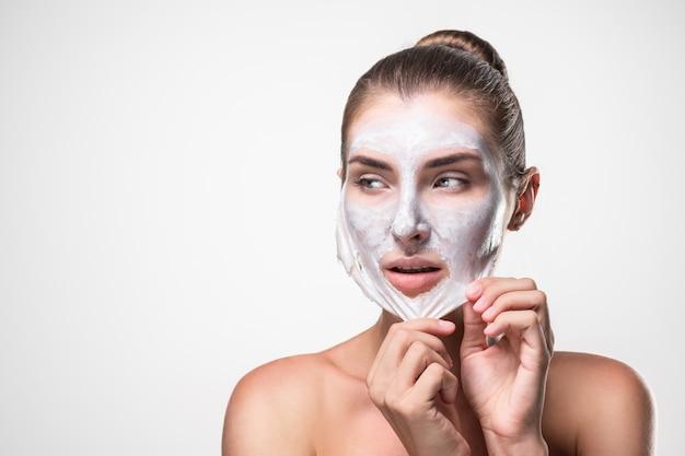 Cosmetici per la cura della pelle di bellezza e concetto di salute. fronte della giovane donna, donna che rimuove la maschera facciale del peel off.