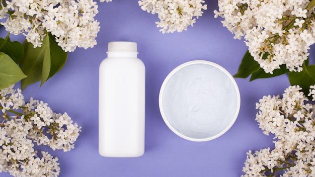 Bellezza, cosmetici bianchi come la neve come la cura della pelle su uno sfondo viola con fiori bianchi di lillà.