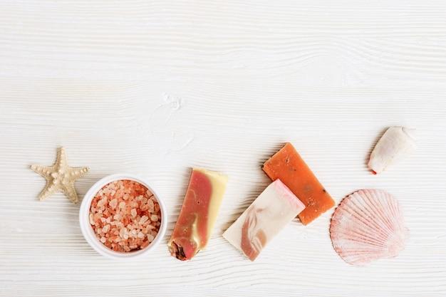 Concetto di bellezza e spa. sapone fatto a mano di colore rosa, sale marino con profumo di rosa, conchiglia, conchiglia, pesce stella su fondo di legno bianco. vista dall'alto e disteso con spazio di copia.