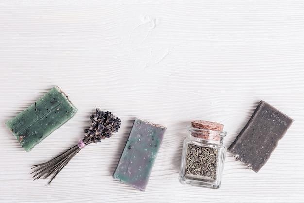 Concetto di bellezza e spa. sapone fatto a mano con erbe profumate naturali e lavanda su fondo di legno bianco. vista dall'alto e disteso con spazio di copia.