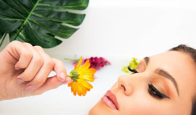 Concetto di bellezza e spa auto indulgenza cura della pelle e del corpo. bella donna con pelle chiara e bel trucco nella vasca da bagno piena di latte con fiori galleggianti.