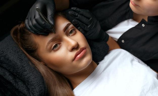 Specialista di bellezza in guanti che stringono le sopracciglia della donna prima della correzione permanente del trucco