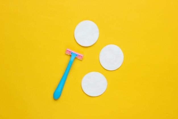 Bellezza ancora in vita, minimalismo. rasoio epilatore in plastica con cerchi in cotone su sfondo giallo. accessori da donna per la cura della bellezza.