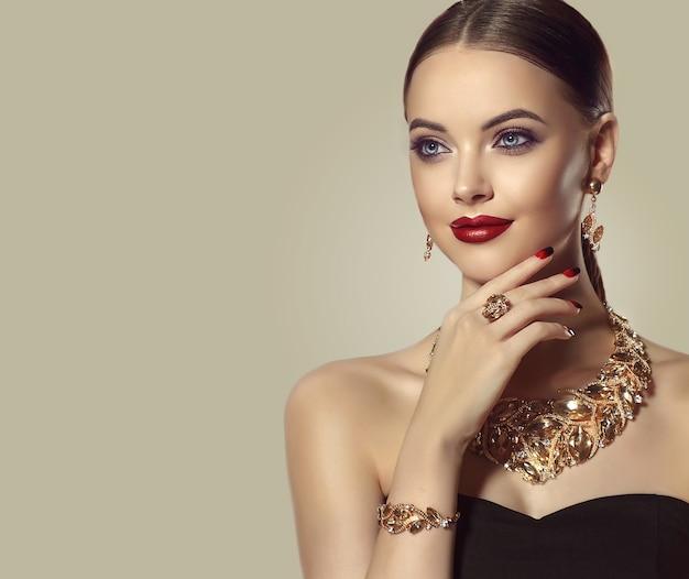 Bella modella dagli occhi azzurri in un elegante trucco da sera sorride dolcemente allo spettatore il set di gioielli con anello di collana e orecchini è vestito su di lei