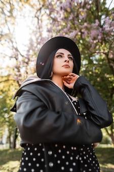 Bellezza soleggiata ritratto donna chic in abito elegante nero in cappello alla moda in giacca di pelle vintage nel parco in giornata di sole luminoso. splendida bella ragazza bruna e luce solare sulla natura in primavera.