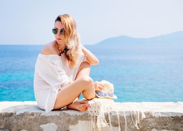 Bellezza abbronzata ed elegante giovane donna in vestiti bianchi, cappello di paglia e occhiali da sole seduti in riva al mare nella soleggiata giornata estiva