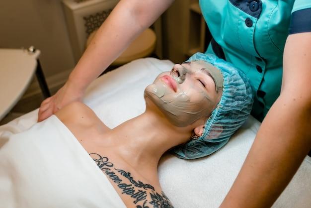 Concetto di trattamento di bellezza. la donna sta ottenendo la maschera facciale al salone della stazione termale