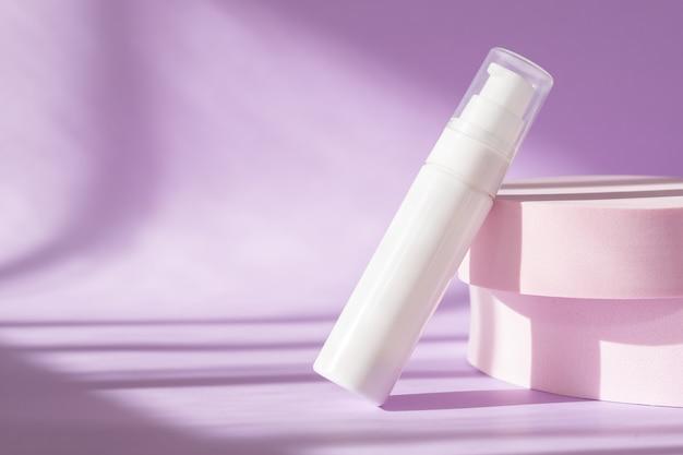 Trattamento di bellezza cura della pelle medica e lozione cosmetica crema siero bottiglia di olio prodotto di imballaggio sulla parete rosa presentazione del prodotto moderna con podio, luce solare, ombra con luce naturale.
