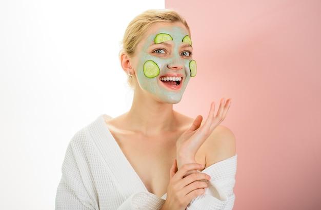 Trattamenti di bellezza dermatologia bella ragazza con maschera per la cura della pelle del viso e fette di cetriolo donna in