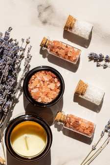 Concetto di bellezza e benessere - sale marino in bottiglie di vetro e candela su vassoio di legno e mazzo di lavanda su fondo di marmo