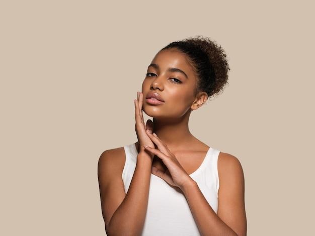 Modello sorridente del viso della pelle nera della donna di bellezza che tocca il suo fronte. colore di sfondo. marrone