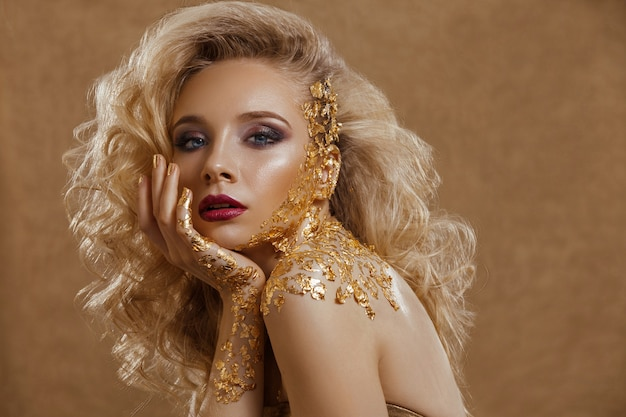 Donna di bellezza, capelli biondi, trucco professionale, colore oro.