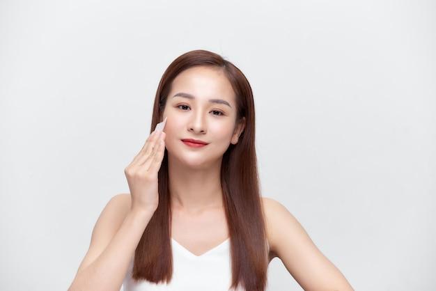 Bellezza. donna che pulisce la pelle fresca perfetta con tessuto assorbente olio, lenzuola.