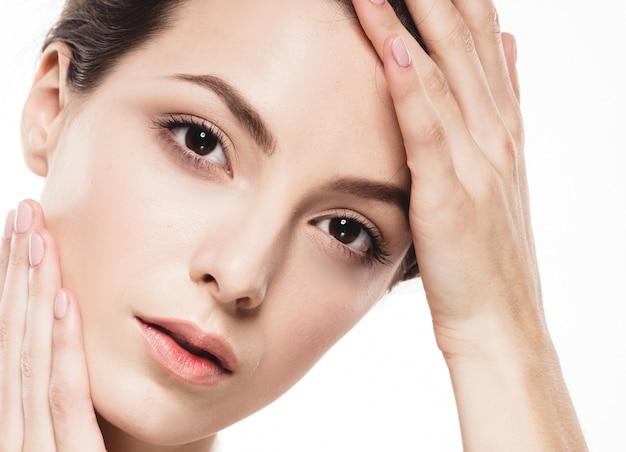 Ritratto del fronte della donna di bellezza. bella ragazza di modello con i capelli corti castana della pelle pulita fresca perfetta gioventù e concetto di cura della pelle. isolato su uno sfondo bianco. colpo di stusio.
