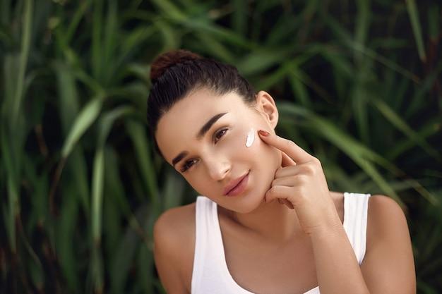 Ritratto di volto di donna di bellezza. la bella ragazza del modello della stazione termale con pelle pulita fresca perfetta applica la crema idratante. cura della pelle. trattamento facciale.