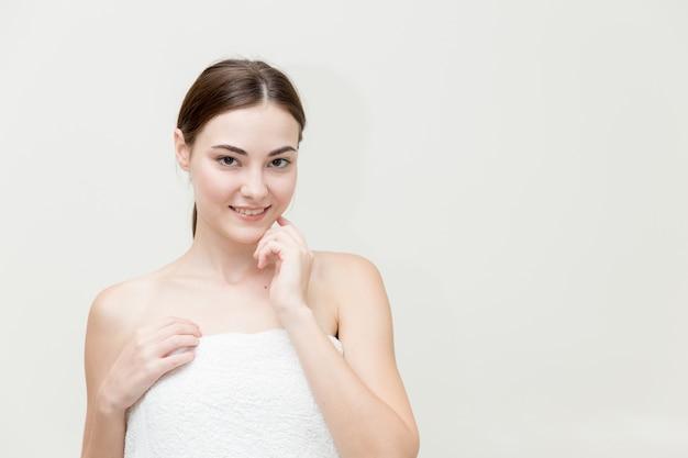 Il fronte della donna di bellezza con la mano presenta la sua forma del fronte isolata sullo studio bianco