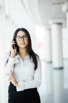 La donna di bellezza in vetri parla al telefono vicino alle finestre panoramiche.