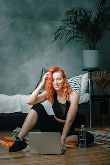La donna di bellezza va a fare sport a casa. allegra donna sportiva con i capelli rossi seduto, sorridendo e guardando nel laptop, sparando blog in camera da letto