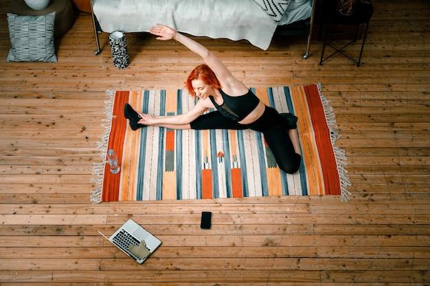 La donna di bellezza va a fare sport a casa. allegra donna sportiva con i capelli rossi si allunga fino alla gamba e guarda nel laptop, sparando al blog in camera da letto