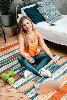 La donna di bellezza va a fare sport a casa