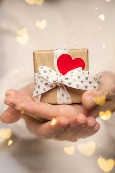 La donna di bellezza passa il contenitore di regalo della tenuta con cuore rosso sul bokeh rosa di incandescenza