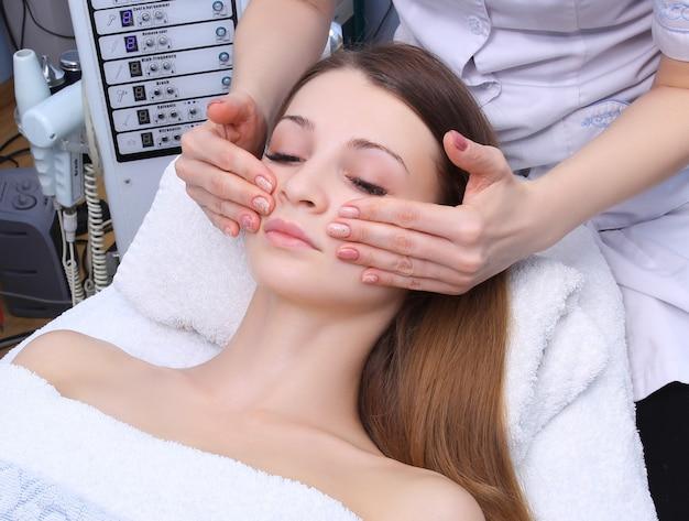 Donna di bellezza con massaggio cosmetico, trattamento viso, primi piani.