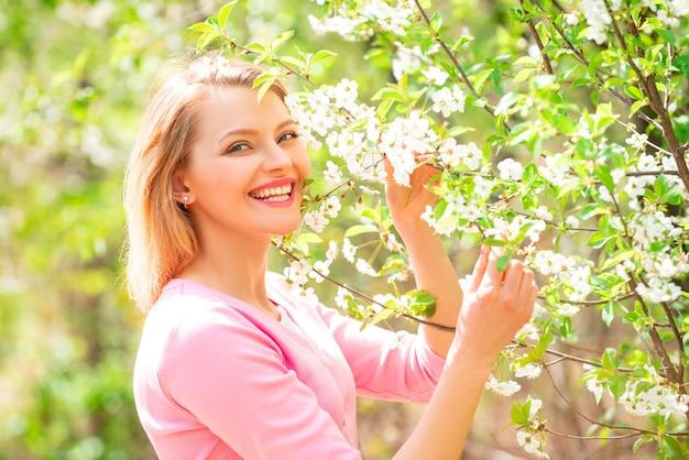 Donna di bellezza che tiene i rami dell'albero in fiore