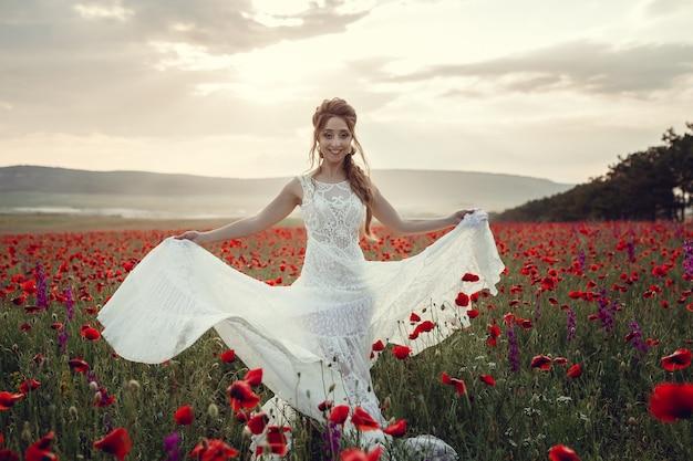 Donna di bellezza nel campo del papavero in vestito bianco. bella sposa in stile boho al tramonto in un campo di papaveri rossi