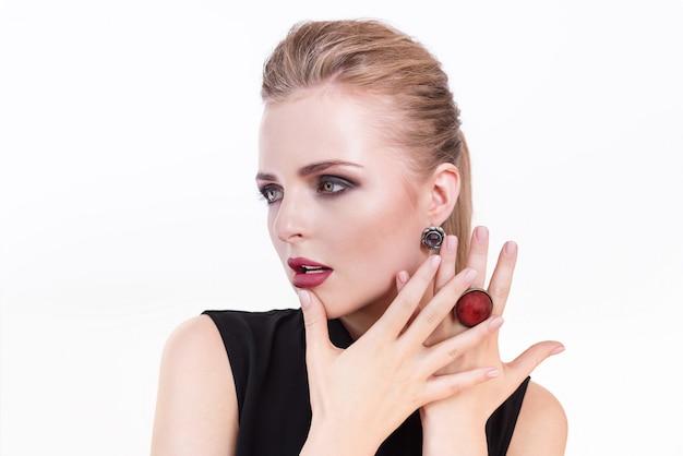 Ritratto di donna di bellezza ragazza bellissima modella con una pelle pulita fresca e perfetta e trucco professionale da sera scura indossando gioielli di moda. femmina bionda che mostra manicure ideale