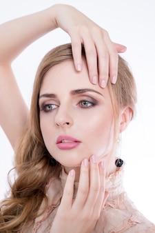 Ritratto di donna di bellezza ragazza bellissima modella con pelle pulita fresca perfetta e trucco professionale. femmina bionda che mostra manicure ideale