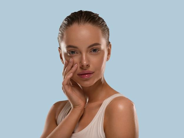 La donna di bellezza con le mani naturali sane compone il fondo di colore di concetto della pelle fresca pulita blu