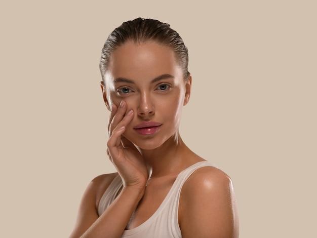 La donna di bellezza con le mani naturali sane compone il fondo di colore di concetto di pelle fresca pulita marrone