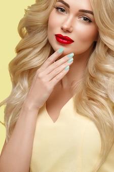 Bellezza donna con lunghi capelli biondi ricci capelli fiore unghie curati colori alla moda arancione e giallo