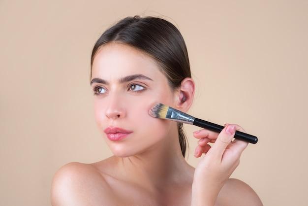 Donna di bellezza con trucco naturale, modello di bellezza fresca con pennello per il trucco. bellissimi cosmetici per il benessere femminile. concetto di cura della pelle della stazione termale. trattamento facciale.
