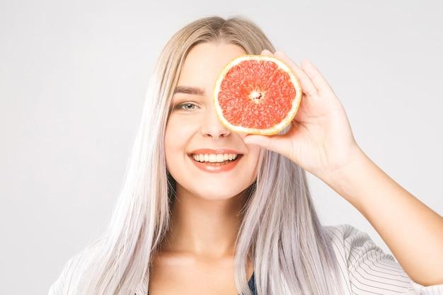 Donna di bellezza con pompelmo di agrumi arancione con corpo sano della pelle