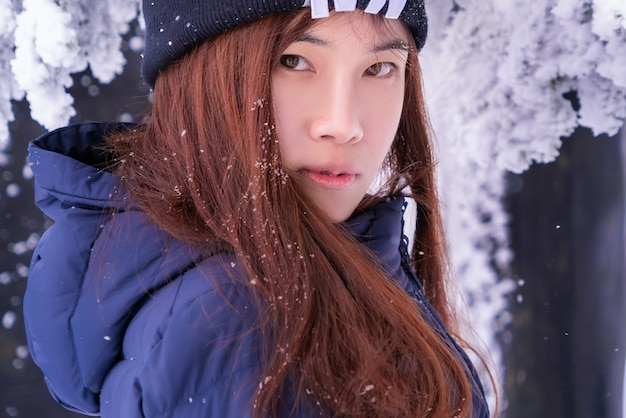 Donna di bellezza con abbigliamento moda inverno nella località sciistica di neve
