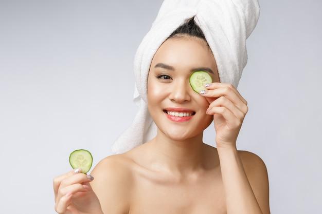Giovane immagine asiatica di cura di pelle delle donne di bellezza con il cetriolo sullo studio bianco del fondo.