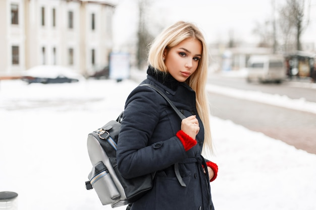 Modello di giovane donna alla moda di bellezza in un cappotto di moda con una borsa alla moda in posa in città
