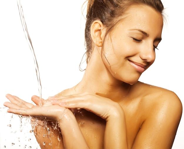 Giovane femmina di bellezza che ha una doccia