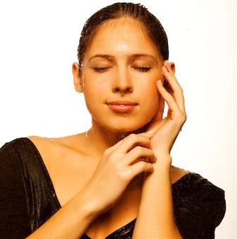 Bellezza giovane donna con gocce d'acqua sul suo viso puro - isolato su bianco