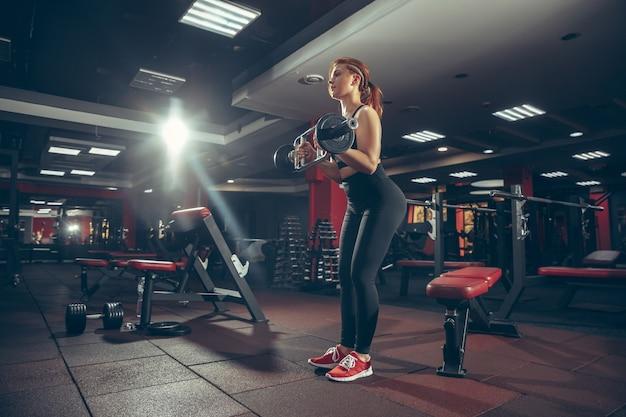 Bellezza. giovane donna caucasica muscolare che pratica in palestra con attrezzature. modello femminile atletico che si esercita, allenando la parte superiore del corpo, allenandosi con il bilanciere. benessere, stile di vita sano, bodybuilding.