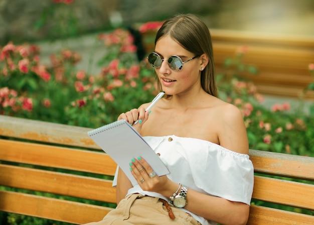 Giovane donna di bellezza in vestiti di estate e occhiali da sole che tengono smartphone